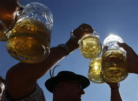 People toast with beer mugs in Munich in this September 21, 2010 file photo. REUTERS/Michaela Rehle