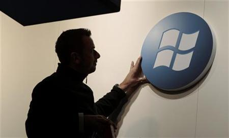 A worker adjusts a logo on the Microsoft stand at the CeBIT computer fair in Hanover in this February 27, 2011 file photo. REUTERS/Tobias Schwarz