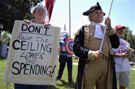Dozens of Tea Party supporters, including one dressed as Captain America (C) and a George Washington impersonator (R), rally near the U.S. Capitol against raising the debt limit in Washington, July 27, 2011. REUTERS/Jonathan Ernst