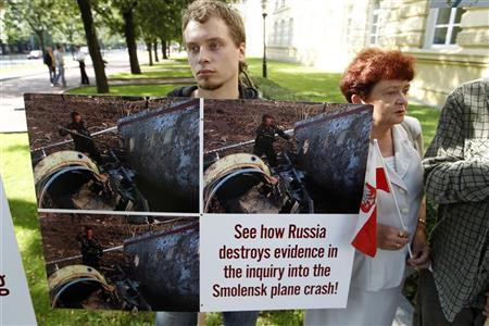 A demonstrator holds a placard depicting pictures as a Polish government commission investigating a plane crash arrives for a news conference at the Prime Minister's Chancellery in Warsaw July 29, 2011. REUTERS/Peter Andrews