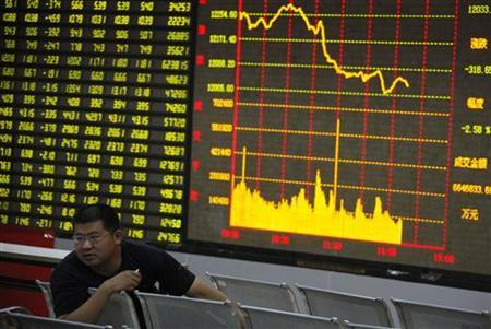 A man sits in front of an electronic board showing stock information at a brokerage house in Huaibei, Anhui province, July 25, 2011. REUTERS/China Daily