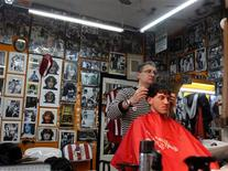 <p>Hairstylist Gerardo Weiss cuts a customer's hair at his hairdressing saloon in Buenos Aires July 29, 2011. REUTERS/Enrique Marcarian</p>