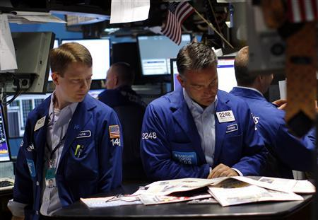 Traders read the morning papers on the main trading floor of the New York Stock Exchange July 29, 2011. . REUTERS/Mike Segar