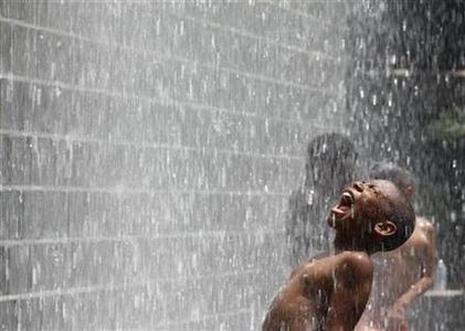 A boy cools off at the Crown Fountain at Millennium Park in Chicago, July 21, 2011. REUTERS/Jim Young
