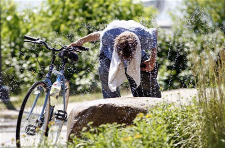 Biker Jordan Richardson, from St. Paul, seeks relief from high temperatures near Lake Calhoun in Minneapolis, July 18, 2011. REUTERS/Eric Miller