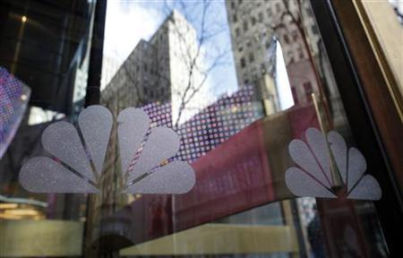 NBC logos are seen on a door with buildings around Rockefeller Center reflected in the background at the home of NBC's studios, in New York, December 3, 2009. REUTERS/Chip East