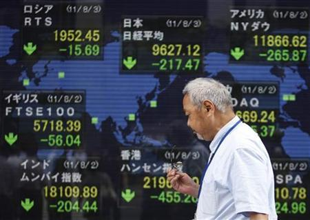 A man walks past an electronic board showing falls in major market indices around the world outside a brokerage in Tokyo August 3, 2011. REUTERS/Yuriko Nakao