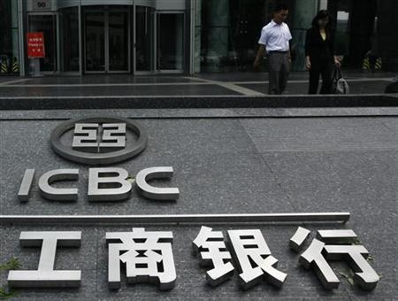 People walk past a company logo of the Industrial and Commercial Bank of China (ICBC) outside one of its branches in Beijing June 18, 2010. REUTERS/Bobby Yip