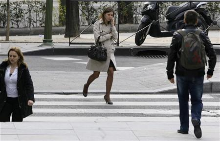 A woman talks on her mobile phone as she walks in Madrid's business district Paseo de la Castellana March 23, 2010. REUTERS/Andrea Comas