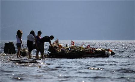 People offer flowers on a memorial stone in Tyrifjorden lake, near Utoeya island, July 31, 2011. REUTERS/Stoyan Nenov