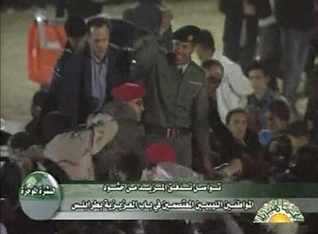 A man (C) resembling Khamis Gaddafi, the son of Libyan leader Muammar Gaddafi, greets supporters in this still image taken from video, March 29, 2011. REUTERS/Libyan TV via Reuters TV