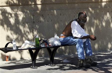 A man removes his shirt to cope with the heat as he sits in the shade in Dallas, Texas August 5, 2011. REUTERS/Mike Stone