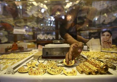 The hand of a Nepalese jewelry store keeper is seen as she arranges gold jewelry in Kathmandu August 8, 2011. REUTERS/Navesh Chitrakar