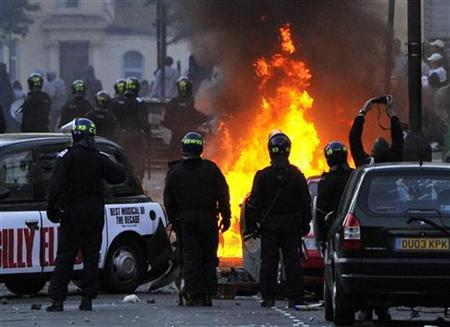 Police officers stand near a barricade of burning and vandalised cars on a street in Hackney, east London August 8, 2011. REUTERS/Toby Melville