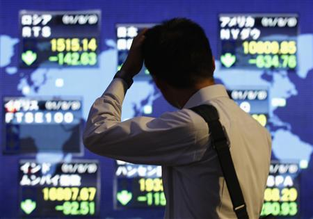 A man scratches his head in front of an electronic board displaying falls in major market indices around the world, outside a brokerage in Tokyo August 9, 2011. REUTERS/Issei Kato