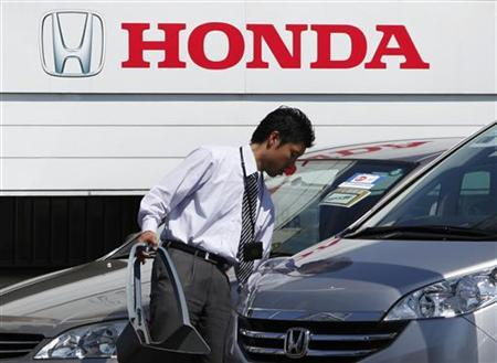 An employee of a Honda dealer prepares to open for business in Kawasaki, south of Tokyo, April 28, 2011. REUTERS/Yuriko Nakao