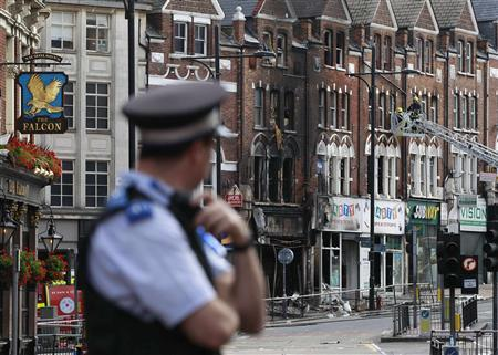 A police officers stands near a burnt out shop in Clapham Junction, in south London August 9, 2011. REUTERS/Stefan Wermuth