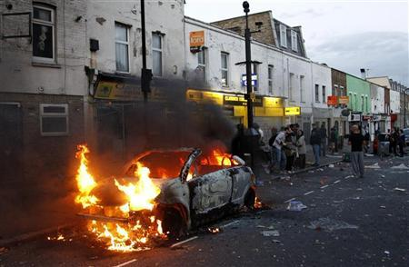 People stand near a burning car in a street in Hackney, east London August 8, 2011. REUTERS/Luke MacGregor