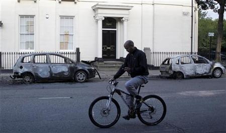 A man looks at his mobile phone as he cycles past two burned out cars in the Toxteth area of Liverpool, northern England August 9, 2011. REUTERS/Phil Noble
