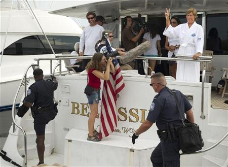 Diana Nyad (R) gestures as U.S. Customs and Border Protection agents board her support boat after she arrived in Key West, Florida, in this handout photograph taken and provided on August 9, 2011. REUTERS/Rob O'Neal/Florida Keys News Bureau/Handout