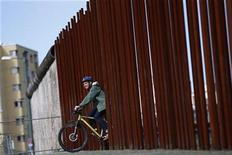 <p>A man rides his bike through a gap in a row of metal rods that delineates the line along which the Berlin Wall used to run at the Berlin Wall memorial site in Bernauer Strasse in Berlin, August 9, 2011. REUTERS/Thomas Peter</p>