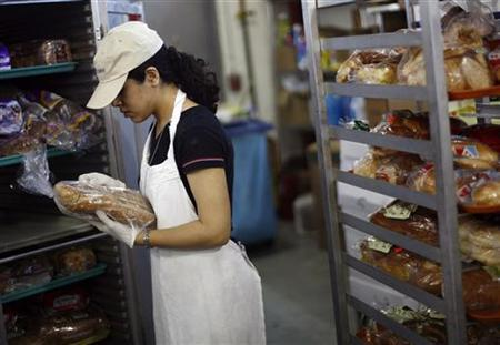 A volunteer worker keeps loaves of bread in a refrigerator inside the Mary Brennan Interfaith Nutrition Network (INN) soup kitchen in Hempstead, New York June 2, 2008. REUTERS/Shannon Stapleton