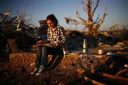 Chanell Gonzalez looks through her grandfather's yearbook which she found in his destroyed home in Joplin, Missouri May 26, 2011. REUTERS/Eric Thayer