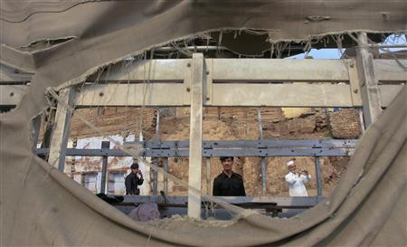 Police are framed through the torn canvas of a vehicle, which was transporting police officials, after it was hit by a bomb in Peshawar August 11, 2011. REUTERS/Khuram Parvez
