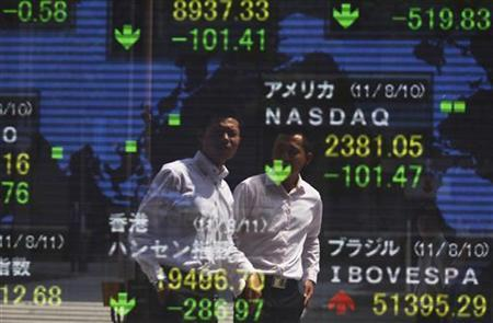 Businessmen are reflected on an electronic board displaying share indices around the world outside a brokerage in Tokyo August 11, 2011. REUTERS/Yuriko Nakao
