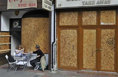 A couple drink at a boarded up wine bar in Ealing, west London August 10, 2011. REUTERS/Toby Melville