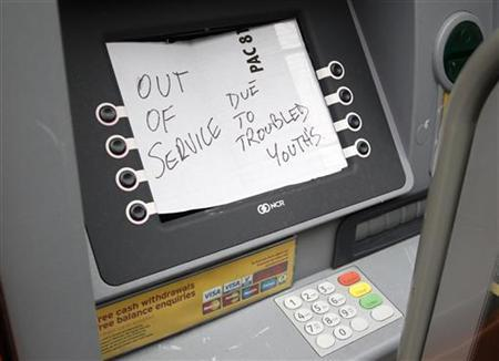 A handwritten notice is attached to a damaged cash machine in Manchester, northern England August 11, 2011. REUTERS/Phil Noble