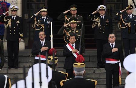 Peru's President Ollanta Humala (C), accompanied by Defense Minister Daniel Mora (L) and Interior Minister Oscar Valdes, attends a ceremony that recognizes him as supreme chief of the Peruvian Armed Forces and the National Police institution, at the government palace in Lima, August 3, 2011. REUTERS/Pilar Olivares