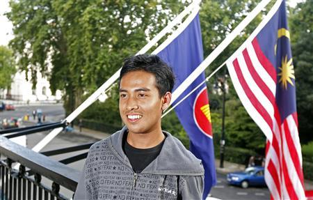 Asyraf Haziq Rosli who was attacked during the London riots, poses for photographs after a news conference at the Malaysian High Commission in London August 11, 2011. REUTERS/Cathal McNaughton