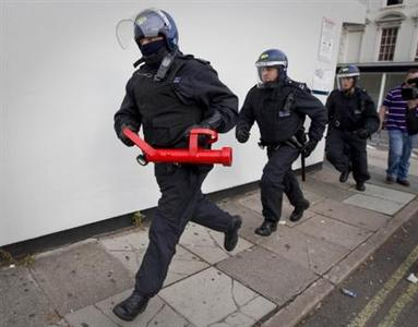 Police officers prepare to raid a property in Pimlico, London August 12, 2011. REUTERS/Peter Nicholls/Pool