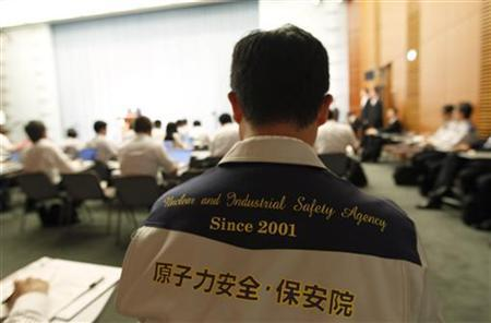 A member of Japan's nuclear and industrial safety agency attends a news conference by Trade Minister Banri Kaieda, whose ministry oversees Japan's nuclear safety agency, and Goshi Hosono, the minister in charge of the government's response to the nuclear crisis, in Tokyo July 19, 2011. REUTERS/Kim Kyung-Hoon