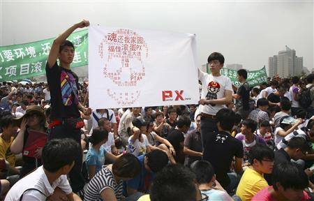 Residents hold a banner with Chinese characters forming a shape of a skull which reads ''Get out PX (paraxylene), give us back our home, never give up'' as they demonstrate against a petrochemical plant at the People's Square in Dalian, Liaoning province August 14, 2011. REUTERS/Stringer