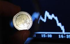 <p>A two euro coin is seen through a magnifying glass near a picture of German share trading DAX index at Frankfurt's stock exchange, in this photo illustration taken in Rome August 8, 2011. REUTERS/Tony Gentile</p>