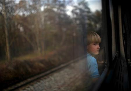 A boy watches through a window of an Amtrak train from Birmingham to Anniston, Alabama November 14, 2009. REUTERS/Carlos Barria