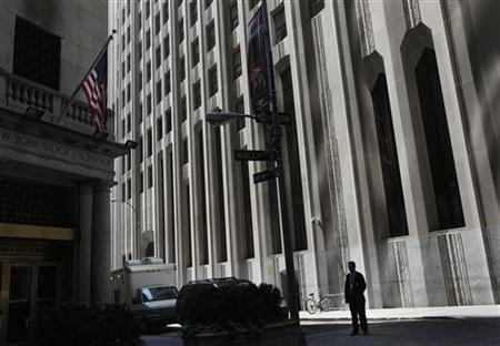 A trader is seen in silhouette outside the New York Stock Exchange August 8, 2011. REUTERS/Shannon Stapleton