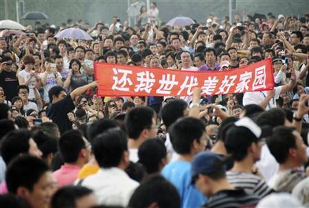 Residents hold a banner among demonstrators protesting against a petrochemical plant at the People's Square in Dalian, Liaoning province August 14, 2011. REUTERS/Stringer