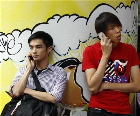 Two men use mobile phones as they wait outside a department store in Hong Kong August 16, 2011. REUTERS/Bobby Yip