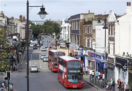 Buses drive along Tottenham High Road on the first day the street had been opened, following riots and looting one week ago in north east London August 13, 2011. REUTERS/Olivia Harris
