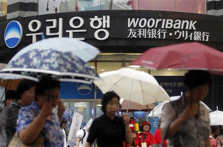 People walk in front of a branch of Woori Bank in Seoul August 17, 2011. REUTERS/Lee Jae-Won
