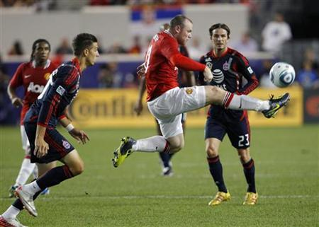 Manchester United's Wayne Rooney (C) leaps to make a pass in front of Major League Soccer (MLS) All-Stars' David Beckham (R) and Geoff Cameron (L) during the MLS All-Star Game at Red Bull Arena in Harrison, New Jersey July 27, 2011. REUTERS/Mike Segar