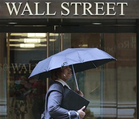 A woman walks through the rain on Wall Street in New York, August 16, 2011. REUTERS/Brendan McDermid
