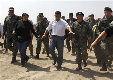 Peru's President Ollanta Humala is accompanied by military officials as he visits the area destroyed by an earthquake four years ago in Pisco August 12, 2011. REUTERS/Mariana Bazo