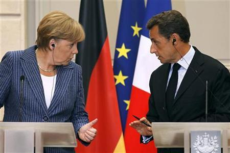 France's President Nicolas Sarkozy (R) and German Chancellor Angela Merkel talk during a news conference at the Elysee Palace in Paris, August 16, 2011. REUTERS/Charles Platiau