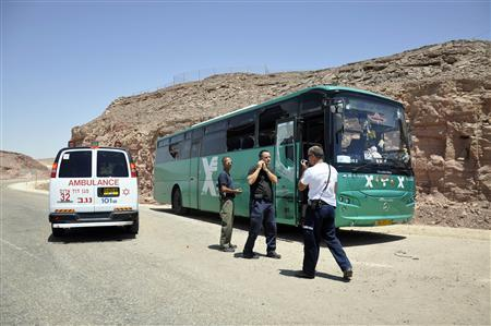 Israeli emergency personnel stand near a bus after it was ambushed about 30 km (18 miles) north of the Red Sea resort of Eilat August 18, 2011. REUTERS/Lior Grundman