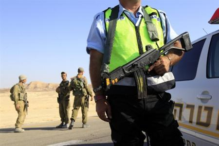 Israeli soldiers and a policeman patrol a road about 60 km (37 miles) from the scene where a bus was ambushed north of the Red Sea resort of Eilat August 18, 2011. REUTERS/Ronen Zvulun