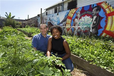 Braham Amadi (L) and Nikki Henderson pose in a community garden behind a low-income housing development in Oakland, California August 13, 2011. REUTERS/Kim White
